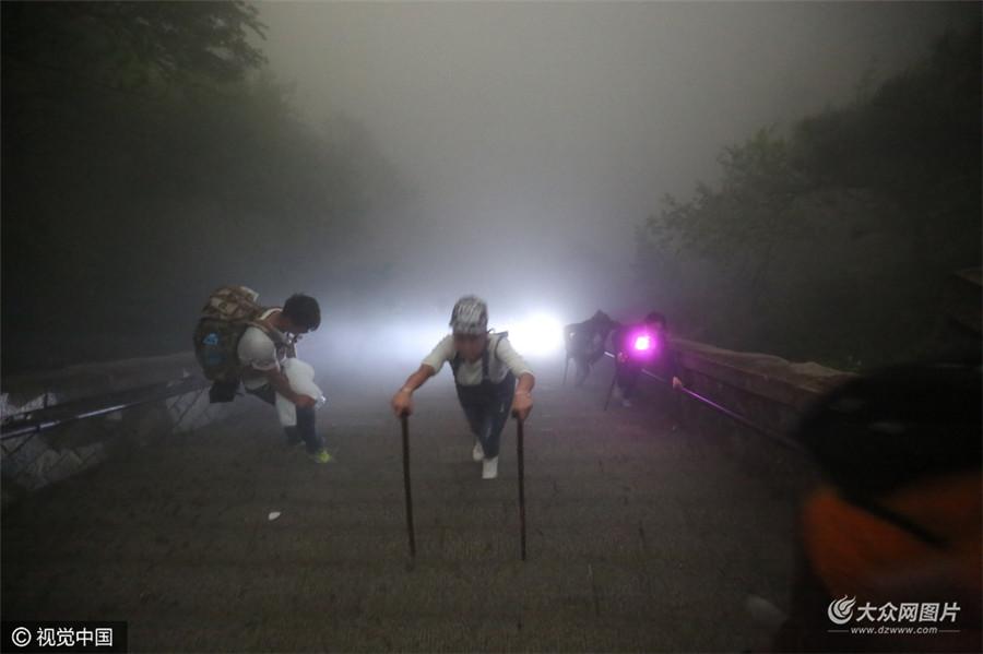 4月30日,山东省泰安市,泰山大雾弥漫能见度最差时为3―4米,游客夜晚雾中登泰山。因夜晚山顶气温较低,不少游客租穿军大衣墙角处避风寒,等待看日出。(图片来源:视觉中国)
