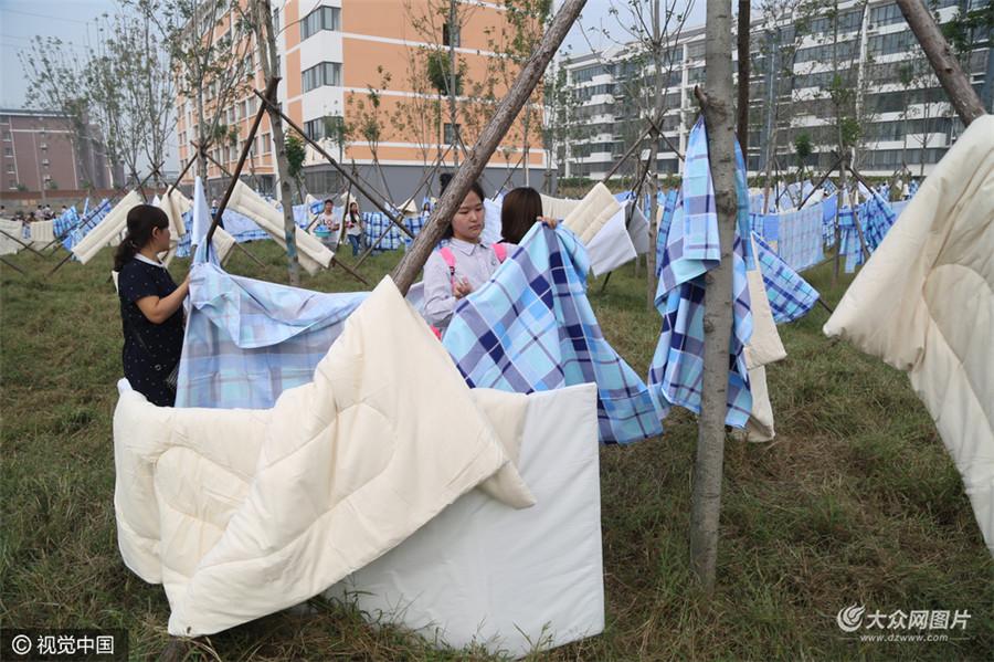 9月11日,山东省泰安市,9月份大学新生报到季,在山东泰山学院宿舍区空地上,密密麻麻地铺满了晾晒的被子和床单。