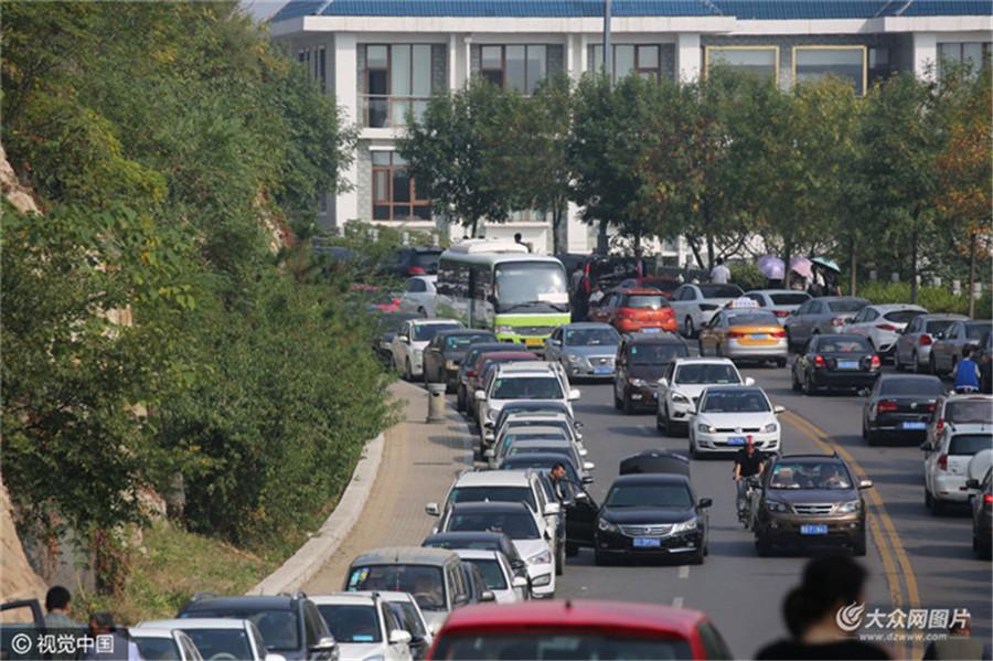 黄金周前三天,来自国内外十多万游客登顶泰山。不少周边省份的游客选择开私家车前来泰山旅游,使得泰山环山路变成临时停车场绵延近5公里,车辆在道路两侧井然有序排列。