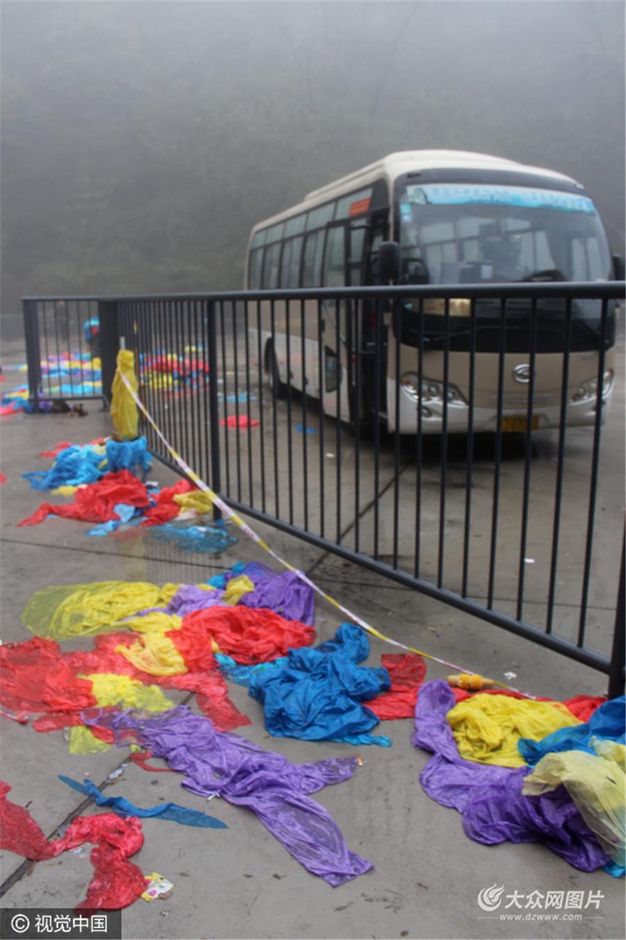 """10月16日,山东省泰安市,泰山景区经受倾盆大雨的洗礼,景区内中天门停车场内,不少游客冒雨登山后将雨衣随手丢弃,并未扔进垃圾箱,停车场顿时变身""""垃圾站""""。"""