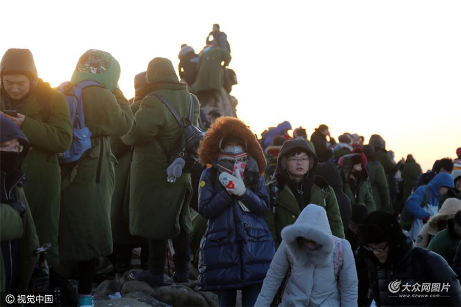 2017年01月01日,山东省泰安市,2017年新年第一天,早上5点多,在泰山山顶日观峰,瞻鲁台等观日点,虽然气温低至零下十多度,山顶一些位置仍有积雪未融化,万余名游客身穿军大衣在寒风中迎接2017新年第一缕曙光。