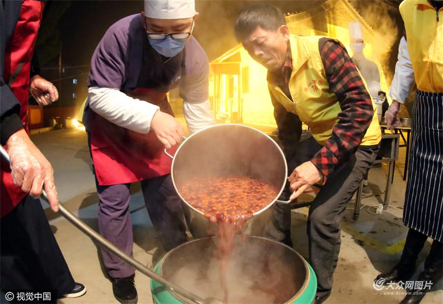 1月4日泰安一座寺庙的师父们借着灯光在寺院内正在加紧熬制传统腊八粥。