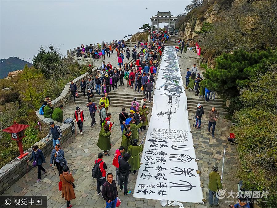 10月14日,山东泰安,在泰山之巅天街上,袁海龙等齐鲁名家运用泼墨、点染、勾勒等技巧,现场一同绘制了长达56米的巨幅山水长卷《大美泰山》,令游人大饱眼福。